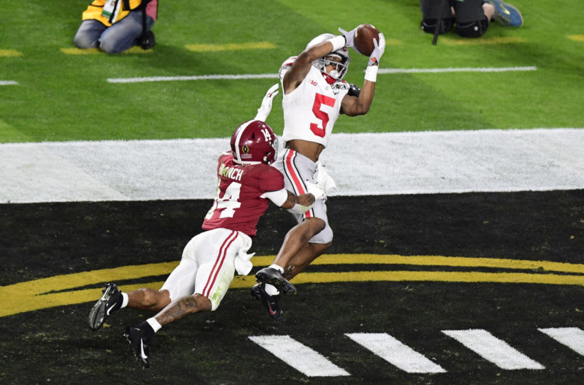Jan 11, 2021; Miami Gardens, FL, USA; Ohio State Buckeyes wide receiver Garrett Wilson (5) catches a touchdown pass against Alabama Crimson Tide defensive back Brian Branch (14) in the third quarter in the 2021 College Football Playoff National Championship Game at Hard Rock Stadium. Mandatory Credit: Douglas DeFelice-USA TODAY Sports