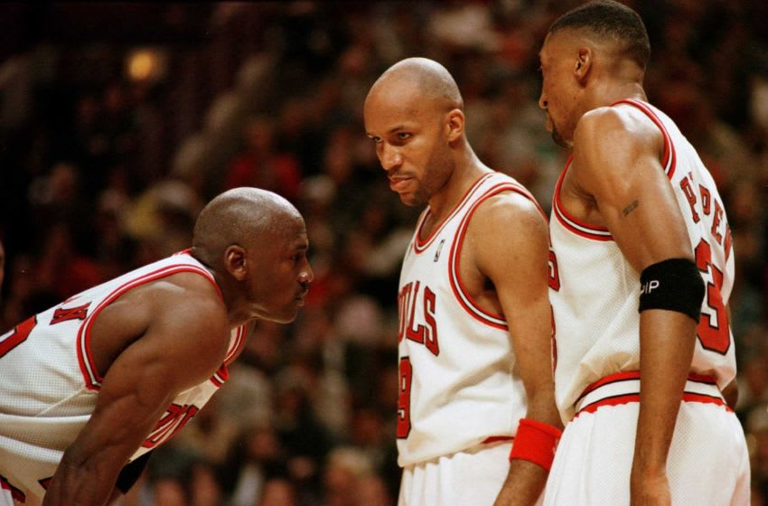 Michael Jordan of the Chicago Bulls discusses strategy with teammates Ron Harper, center, and Scottie Pippen during a time-out on the court during Game 2 in the NBA Finals