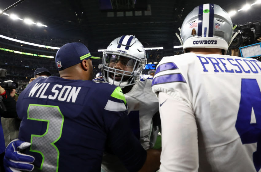 ARLINGTON, TEXAS - JANUARY 05: Ezekiel Elliott #21 and Dak Prescott #4 of the Dallas Cowboys talks with Russell Wilson #3 of the Seattle Seahawks after the Cowboys defeated the Seahawks 24-22 in the Wild Card Round at AT&T Stadium on January 05, 2019 in Arlington, Texas. (Photo by Ronald Martinez/Getty Images)