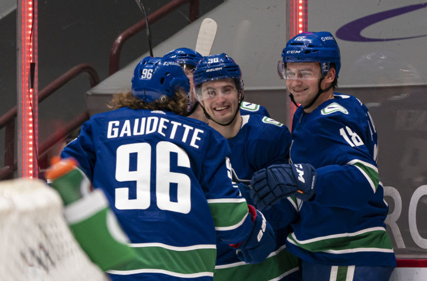 VANCOUVER, BC - MARCH 04: Jake Virtanen #18 of the Vancouver Canucks celebrates his goal against the Toronto Maple Leafs with teammates Adam Gaudette #96 and Nils Hoglander #36 during NHL hockey action at Rogers Arena on March 4, 2021 in Vancouver, Canada. (Photo by Rich Lam/Getty Images)