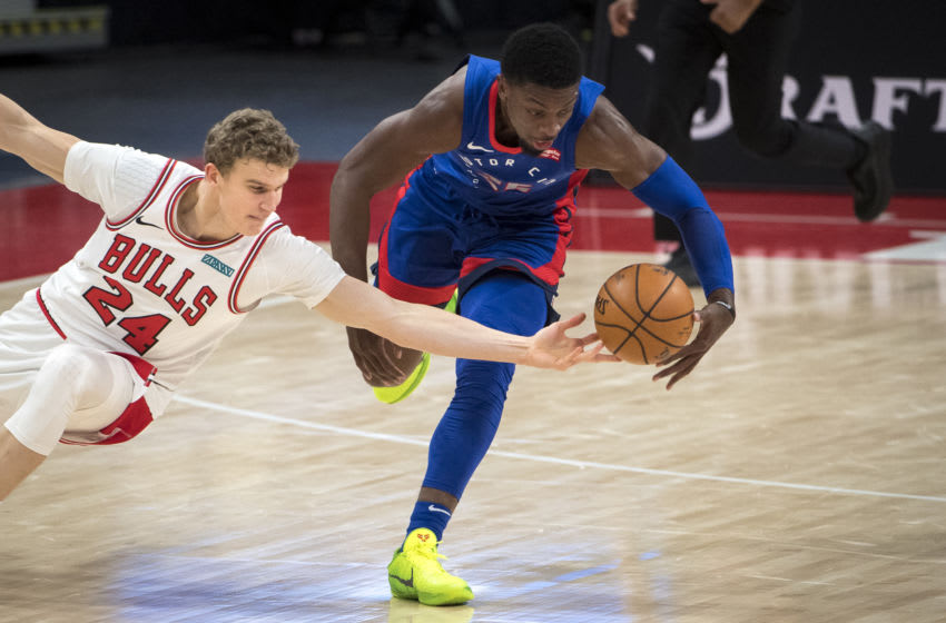 DETROIT, MICHIGAN - MARCH 21: Lauri Markkanen #24 of the Chicago Bulls and Tyler Cook #25 the Detroit Pistons reach for a loose ball during the second quarter of the game at Little Caesars Arena on March 21, 2021 in Detroit, Michigan. NOTE TO USER: User expressly acknowledges and agrees that, by downloading and or using this photograph, User is consenting to the terms and conditions of the Getty Images License Agreement. (Photo by Nic Antaya/Getty Images)
