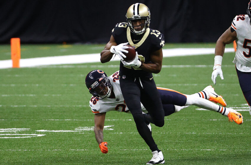 NEW ORLEANS, LOUISIANA - JANUARY 10: Michael Thomas #13 of the New Orleans Saints runs through a tackle by Deon Bush #26 of the Chicago Bears during the first quarter in the NFC Wild Card Playoff game at Mercedes Benz Superdome on January 10, 2021 in New Orleans, Louisiana. (Photo by Chris Graythen/Getty Images)