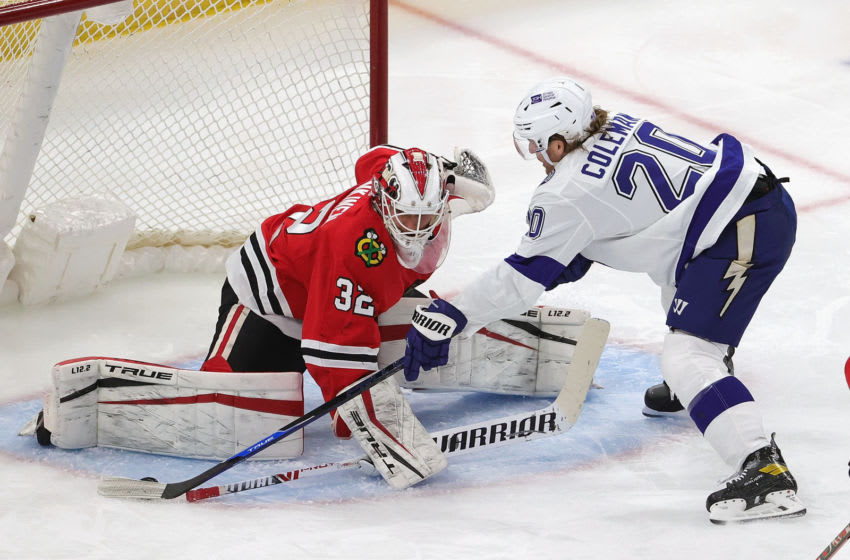 CHICAGO, ILLINOIS - MARCH 07: Kevin Lankinen #32 of the Chicago Blackhawks stops a shot by Blake Coleman #20 of the Tampa Bay Lightning at the United Center on March 07, 2021 in Chicago, Illinois. (Photo by Jonathan Daniel/Getty Images)