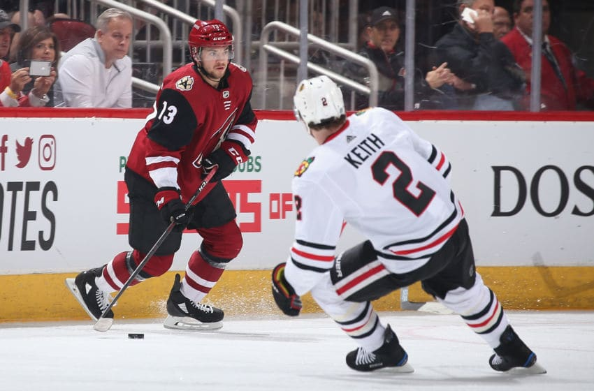 GLENDALE, ARIZONA - MARCH 26: Vinnie Hinostroza #13 of the Arizona Coyotes skates with the puck ahead of Duncan Keith #2 of the Chicago Blackhawks during the first period of the NHL game at Gila River Arena on March 26, 2019 in Glendale, Arizona. (Photo by Christian Petersen/Getty Images)