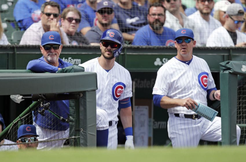 CHICAGO, ILLINOIS - AUGUST 31: (L-R) Manager Joe Maddon #70, Kris Bryant #17, and bench coach Mark Loretta #19 of the Chicago Cubs stand in their dugout during the first inning of a game against the Milwaukee Brewers at Wrigley Field on August 31, 2019 in Chicago, Illinois. (Photo by Nuccio DiNuzzo/Getty Images)