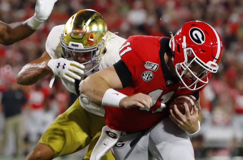 ATHENS, GEORGIA - SEPTEMBER 21: Jake Fromm #11 of the Georgia Bulldogs battles for yards while being tackled by Alohi Gilman #11 of the Notre Dame Fighting Irish at Sanford Stadium on September 21, 2019 in Athens, Georgia. (Photo by Kevin C. Cox/Getty Images)