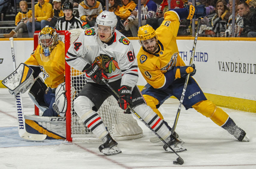 NASHVILLE, TENNESSEE - NOVEMBER 16: David Kampf #64 of the Chicago Blackhawks carries the puck away from Filip Forsberg #9 of the Nashville Predators during the second period at Bridgestone Arena on November 16, 2019 in Nashville, Tennessee. (Photo by Frederick Breedon/Getty Images)