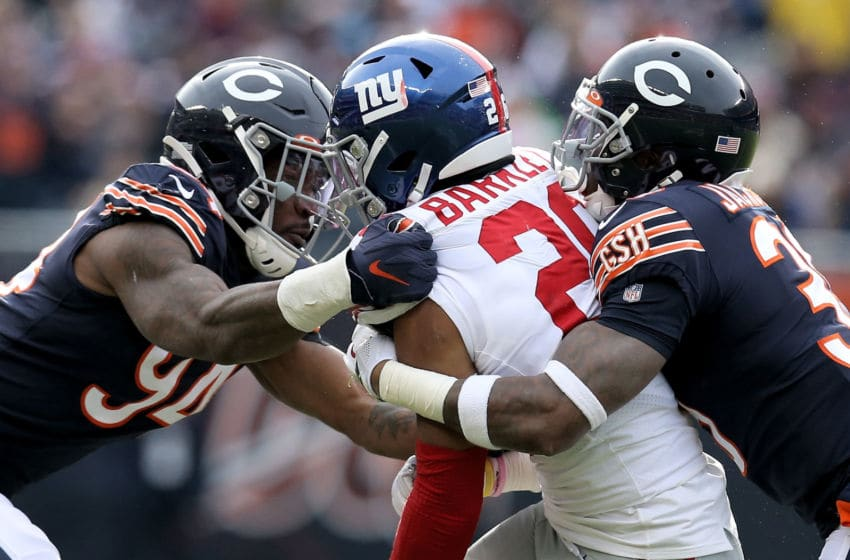 CHICAGO, ILLINOIS - NOVEMBER 24: Saquon Barkley #26 of the New York Giants runs with the ball while being tackled by Leonard Floyd #94 and Eddie Jackson #39 of the Chicago Bears in the second quarter at Soldier Field on November 24, 2019 in Chicago, Illinois. (Photo by Dylan Buell/Getty Images)