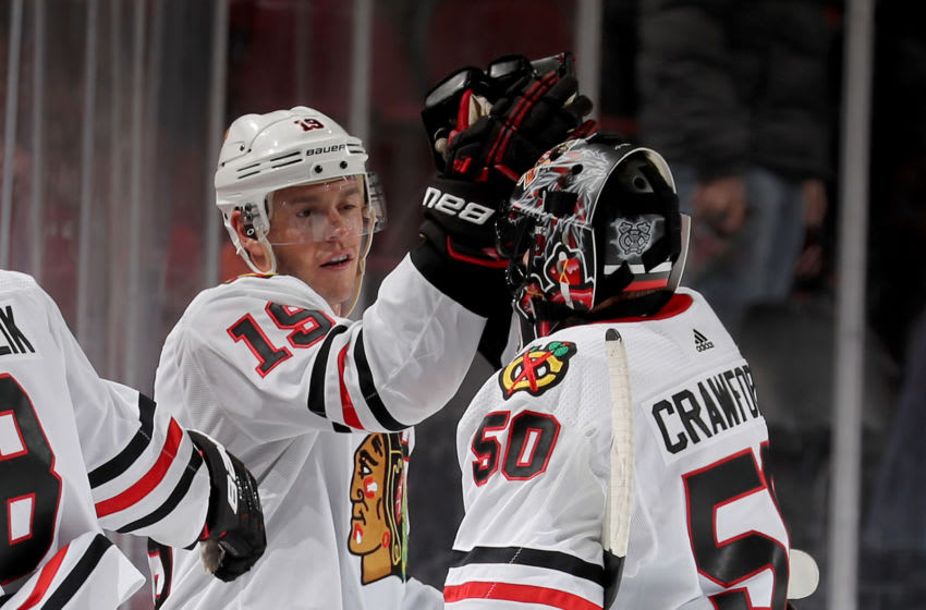 NEWARK, NEW JERSEY - DECEMBER 06: Jonathan Toews #19 of the Chicago Blackhawks congratulates Corey Crawford #50 after the win over the New Jersey Devils at Prudential Center on December 06, 2019 in Newark, New Jersey.The Chicago Blackhawks defeated the New Jersey Devils 2-1 in a shootout. (Photo by Elsa/Getty Images)
