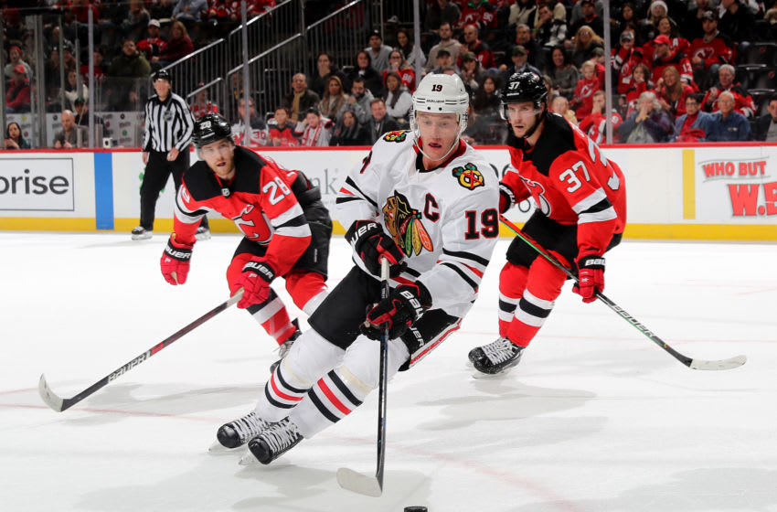 NEWARK, NEW JERSEY - DECEMBER 06: Jonathan Toews #19 of the Chicago Blackhawks takes the puck as Damon Severson #28 and Pavel Zacha #37 of the New Jersey Devils defend at Prudential Center on December 06, 2019 in Newark, New Jersey.The Chicago Blackhawks defeated the New Jersey Devils 2-1 in a shootout. (Photo by Elsa/Getty Images)
