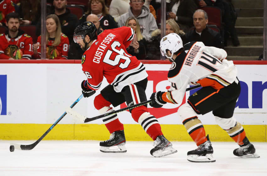 CHICAGO, ILLINOIS - JANUARY 11: Erik Gustafsson #56 of the Chicago Blackhawks advances the puck in front of Adam Henrique #14 of the Anaheim Ducks at the United Center on January 11, 2020 in Chicago, Illinois. (Photo by Jonathan Daniel/Getty Images)