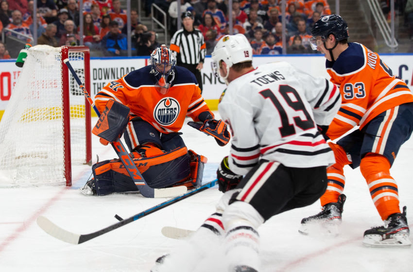 EDMONTON, AB - FEBRUARY 11: Goaltender Mike Smith #41 of the Edmonton Oilers stops Jonathan Toews #19 of the Chicago Blackhawks at Rogers Place on February 11, 2020, in Edmonton, Canada. (Photo by Codie McLachlan/Getty Images)