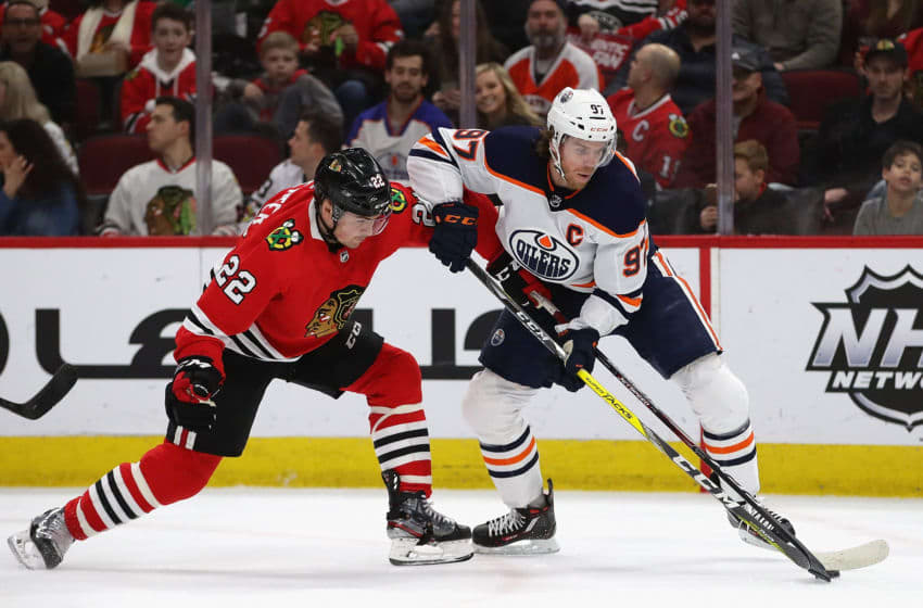 CHICAGO, ILLINOIS - MARCH 05: Connor McDavid #97 of the Edmonton Oilers is pressured by Ryan Carpenter #22 of the Chicago Blackhawks as he advances the puck at the United Center on March 05, 2020 in Chicago, Illinois. (Photo by Jonathan Daniel/Getty Images)