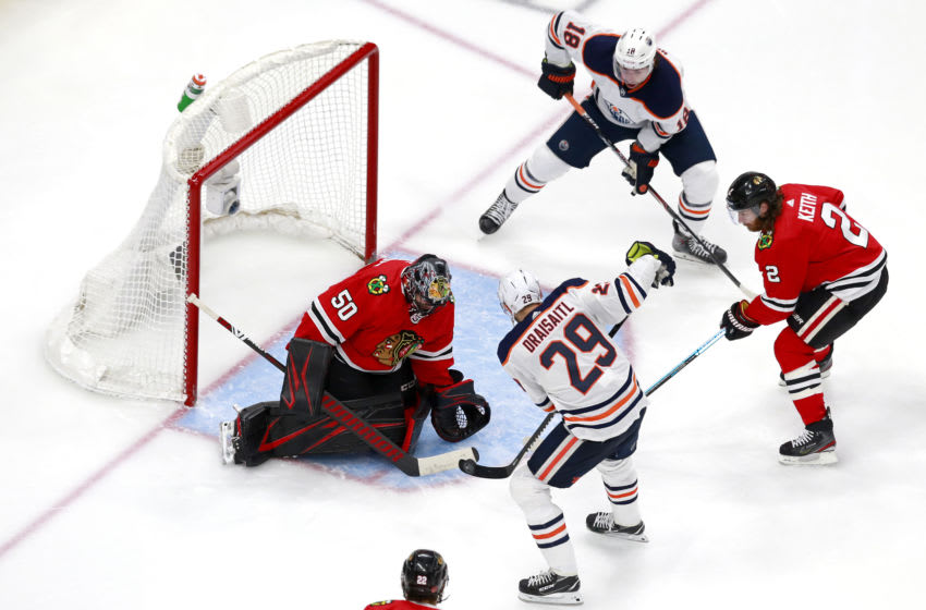 EDMONTON, ALBERTA - AUGUST 07: Corey Crawford #50 of the Chicago Blackhawks defends a shot against Leon Draisaitl #29 of the Edmonton Oilers during the third period in Game Four of the Western Conference Qualification Round prior to the 2020 NHL Stanley Cup Playoffs at Rogers Place on August 07, 2020 in Edmonton, Alberta. (Photo by Jeff Vinnick/Getty Images)