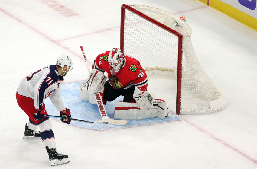 CHICAGO, ILLINOIS - JANUARY 29: Kevin Lankinen #32 of the Chicago Blackhawks blocks a shot by Nick Foligno #71 of the Columbus Blue Jackets during the third period at the United Center on January 29, 2021 in Chicago, Illinois. (Photo by Stacy Revere/Getty Images)