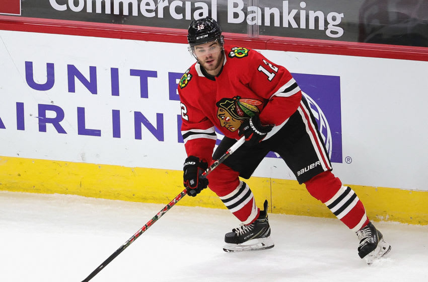 CHICAGO, ILLINOIS - FEBRUARY 02: Alex DeBrincat #12 of the Chicago Blackhawks looks to pass against the Carolina Hurricanes at the United Center on February 02, 2021 in Chicago, Illinois. (Photo by Jonathan Daniel/Getty Images)