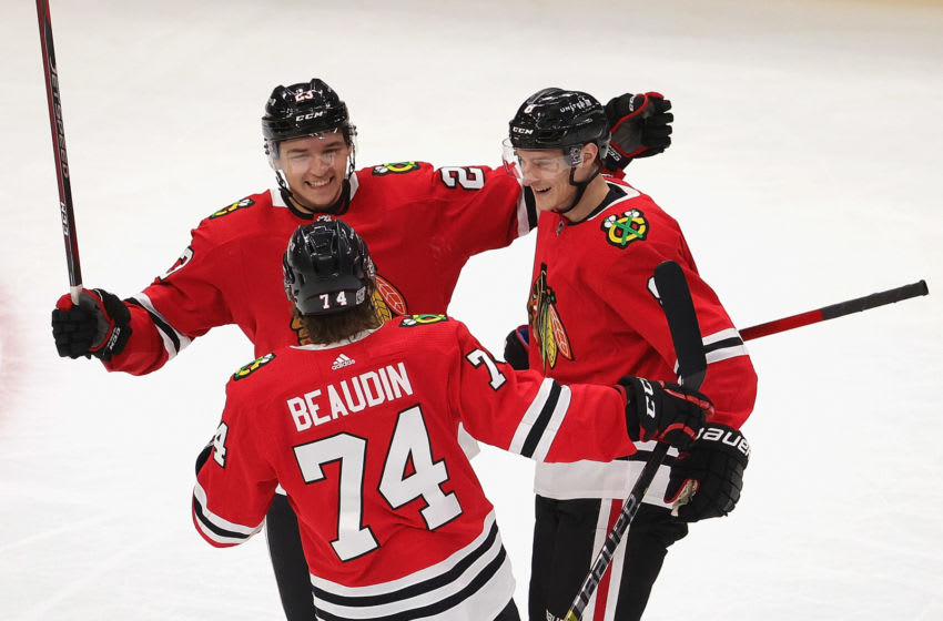 CHICAGO, ILLINOIS - FEBRUARY 04: Dominik Kubalik #8 of the Chicago Blackhawks (R) is greeted by Philipp Kurashev #23 and Nicolas Beaudin #74 after scoring a first period goal against the Carolina Hurricanes at the United Center on February 04, 2021 in Chicago, Illinois. (Photo by Jonathan Daniel/Getty Images)