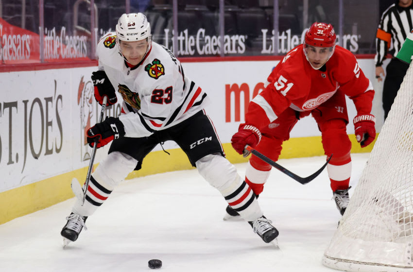 DETROIT, MICHIGAN - FEBRUARY 17: Philipp Kurashev #23 of the Chicago Blackhawks controls the puck in front of Valtteri Filppula #51 of the Detroit Red Wings during the first period at Little Caesars Arena on February 17, 2021 in Detroit, Michigan. (Photo by Gregory Shamus/Getty Images)