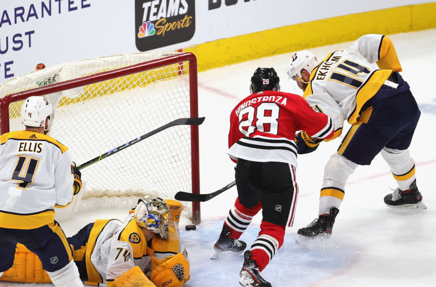CHICAGO, ILLINOIS - APRIL 23: Vinnie Hinostroza #28 of the Chicago Blackhawks scores a third period goal against Juuse Saros #74 and Mattias Ekholm #14 of the Nashville Predators at the United Center on April 23, 2021 in Chicago, Illinois. The Predators defeated the Blackhawks 3-1. (Photo by Jonathan Daniel/Getty Images)