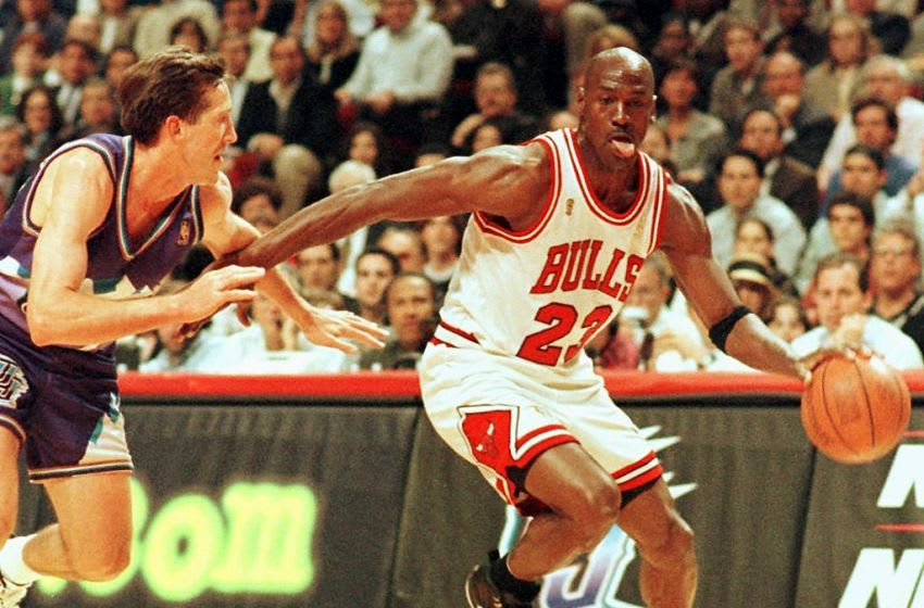 CHICAGO, UNITED STATES: Chicago Bulls player Michael Jordan sticks out his tongue as he goes past Jeff Hornacek of the Utah Jazz 04 June during game two of the NBA Finals at the United Center in Chicago, IL. The Bulls lead the best-of-seven series 1-0. AFP PHOTO/Vincent LAFORET (Photo credit should read VINCENT LAFORET/AFP via Getty Images)