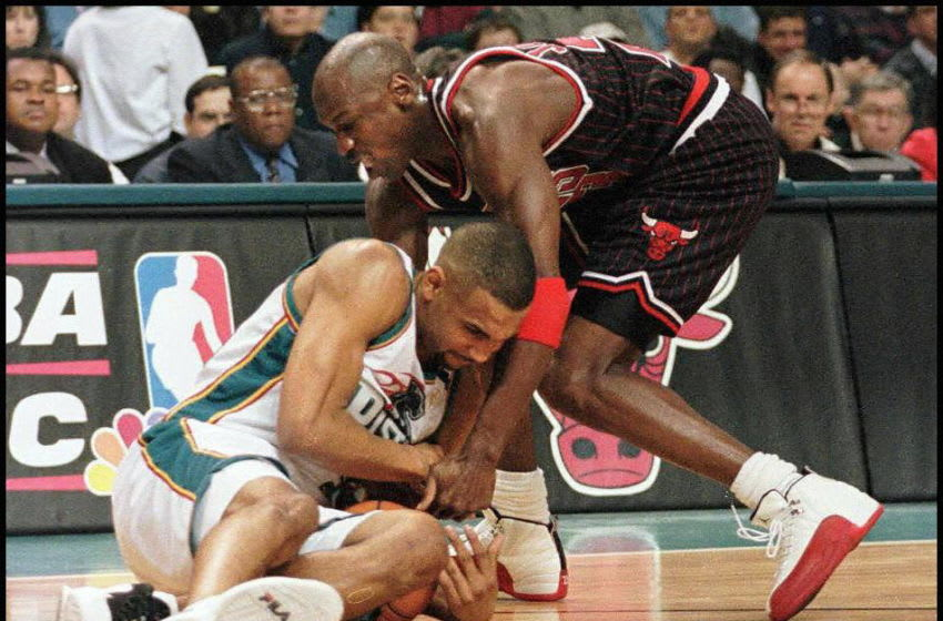 AUBURN HILLS, UNITED STATES: Grant Hill of the Detroit Pistons (L) and Michael Jordan of the Chicago Bulls (R) fight for a loose ball in the first quarter of their 13 April game at the Palace in Auburn Hills, Michigan. (Photo credit should read MATT CAMPBELL/AFP via Getty Images)