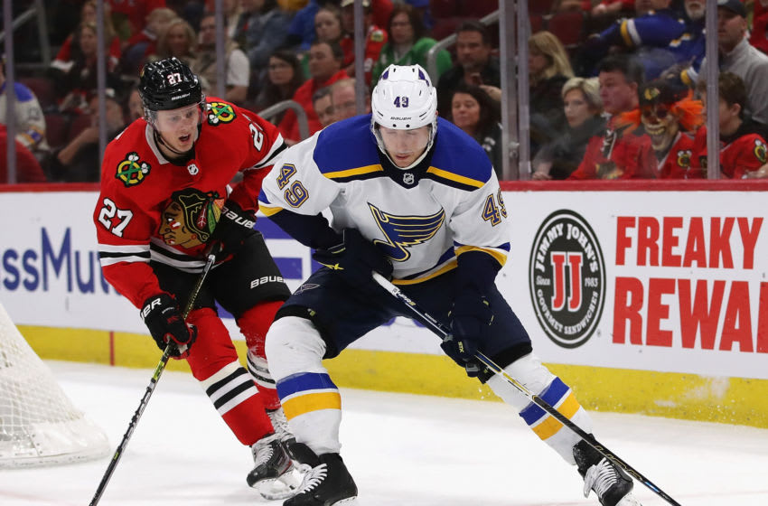 CHICAGO, ILLINOIS - MARCH 08: Ivan Barbashev #49 of the St. Louis Blues Turns with the puck under pressure from Adam Boqvist #27 of the Chicago Blackhawks at the United Center on March 08, 2020 in Chicago, Illinois. (Photo by Jonathan Daniel/Getty Images)