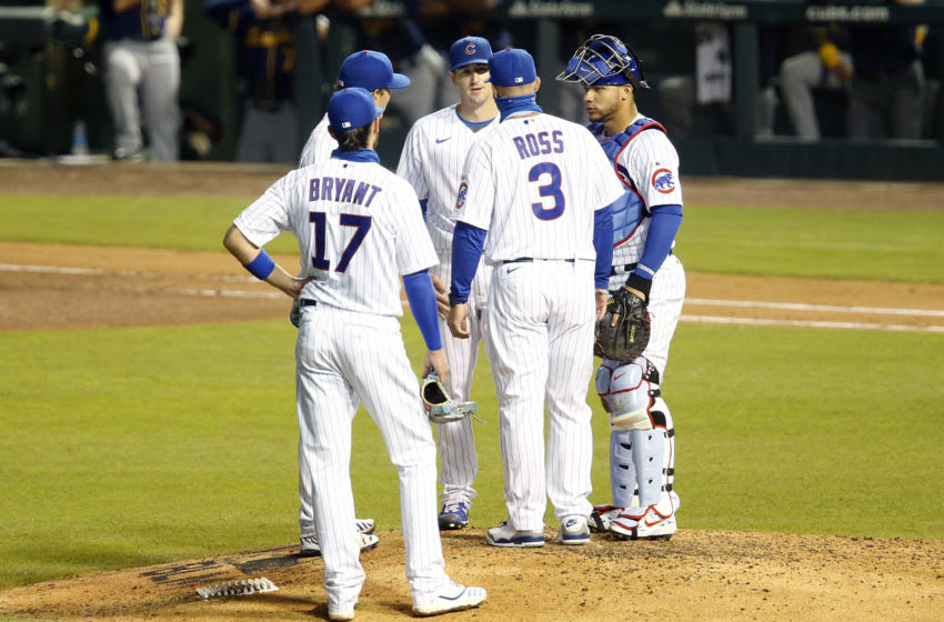 CHICAGO, ILLINOIS - JULY 24: Manger David Ross #3 of the Chicago Cubs talks with Kyle Hendricks #28 of the Chicago Cubs on the mound in the game against the Milwaukee Brewers on opening day at Wrigley Field on July 24, 2020 in Chicago, Illinois. The 2020 season had been postponed since March due to the COVID-19 pandemic. (Photo by Justin Casterline/Getty Images)