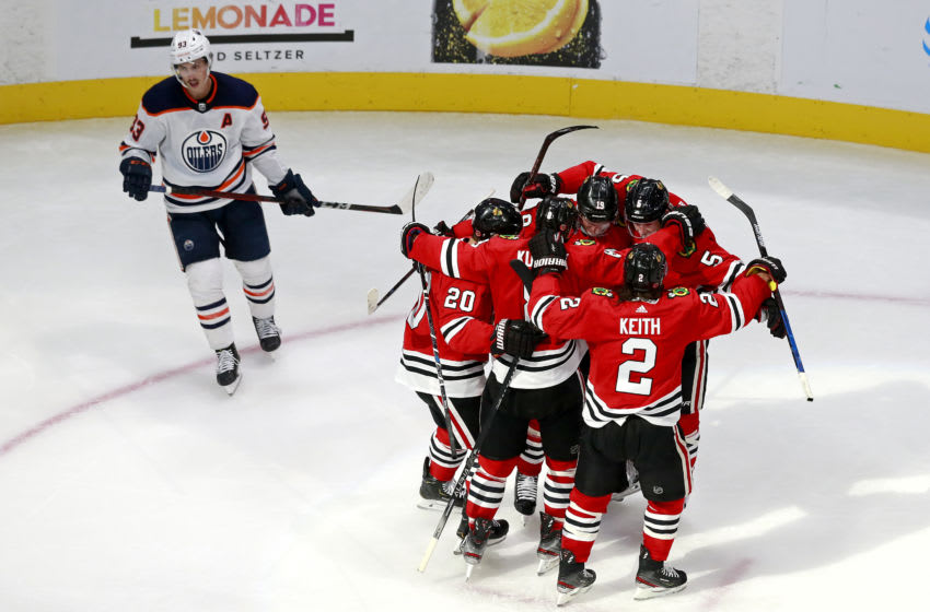 EDMONTON, ALBERTA - AUGUST 05: Connor Murphy #5 of the Chicago Blackhawks is congratulated by his teammates after scoring a go-ahead goal as Ryan Nugent-Hopkins #93 of the Edmonton Oilers reacts during the third period in Game Three of the Western Conference Qualification Round prior to the 2020 NHL Stanley Cup Playoffs at Rogers Place on August 05, 2020 in Edmonton, Alberta. (Photo by Jeff Vinnick/Getty Images)