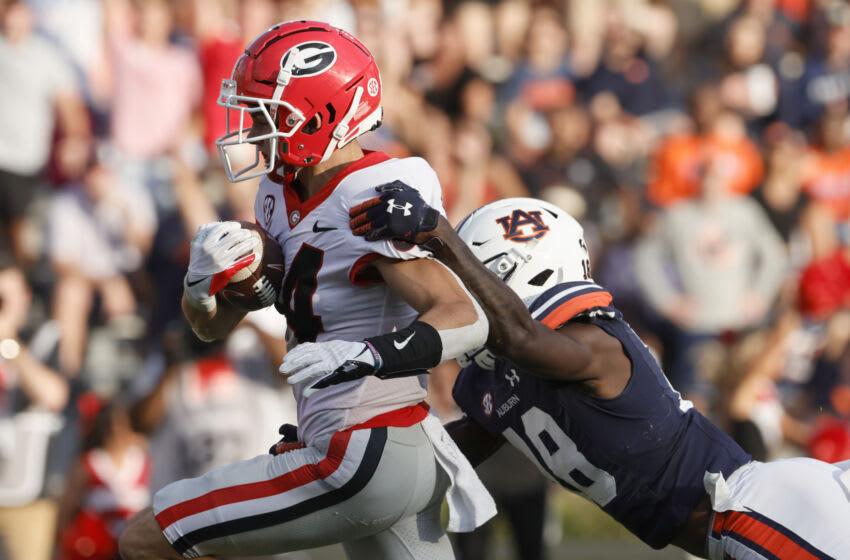 Oct 9, 2021; Auburn, Alabama, USA; Georgia Bulldogs wide receiver Ladd McConkey (84) drags Auburn Tigers cornerback Nehemiah Pritchett (18) into the end zone during the third quarter at Jordan-Hare Stadium. Mandatory Credit: John Reed-USA TODAY Sports