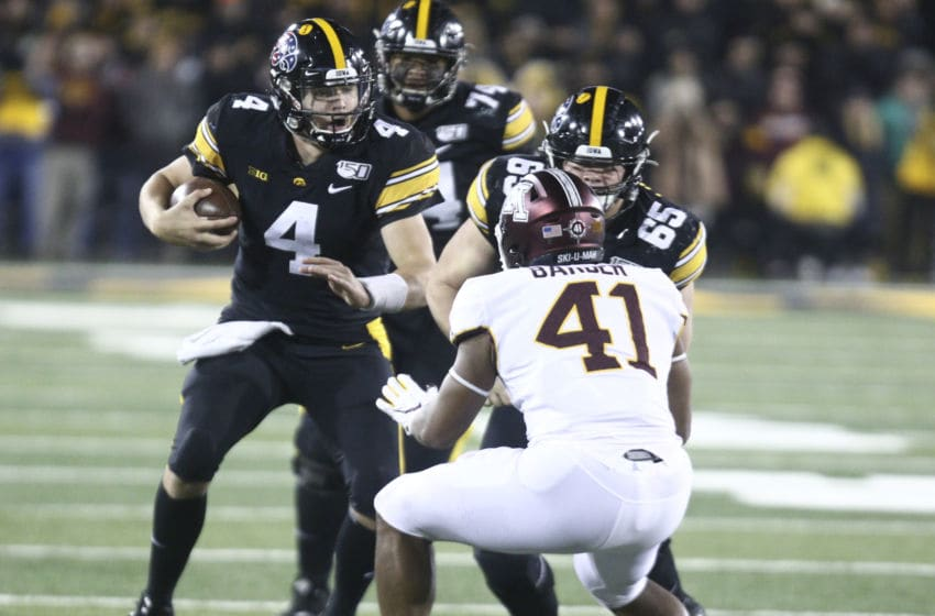 IOWA CITY, IOWA- NOVEMBER 16: Quarterback Nate Stanley #4 of the Iowa Hawkeyes rushes up field on a keeper during the second half in front of linebacker Thomas Barber #41 of the Minnesota Gophers on November 16, 2019 at Kinnick Stadium in Iowa City, Iowa. (Photo by Matthew Holst/Getty Images)