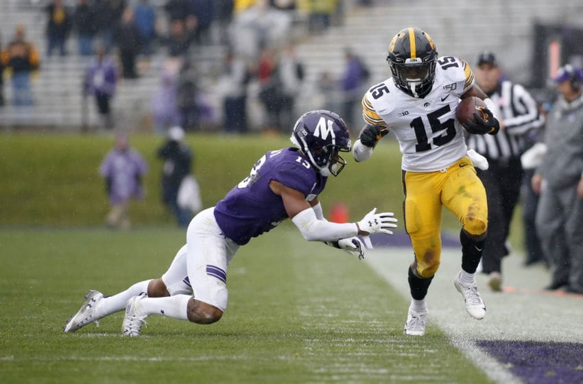 EVANSTON, ILLINOIS - OCTOBER 26: Tyler Goodson #15 of the Iowa Hawkeyes runs the ball while being pushed out of bounds by JR Pace #13 of the Northwestern Wildcats during the fourth quarter at Ryan Field on October 26, 2019 in Evanston, Illinois. (Photo by Justin Casterline/Getty Images)