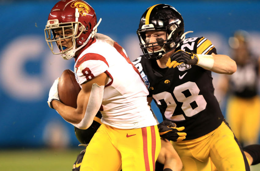 SAN DIEGO, CALIFORNIA - DECEMBER 27: Amon-Ra St. Brown #8 of the USC Trojans eludes Jack Koerner #28 of the Iowa Hawkeyes on a pass play during the second half of the San Diego County Credit Union Holiday Bowl at SDCCU Stadium on December 27, 2019 in San Diego, California. (Photo by Sean M. Haffey/Getty Images)