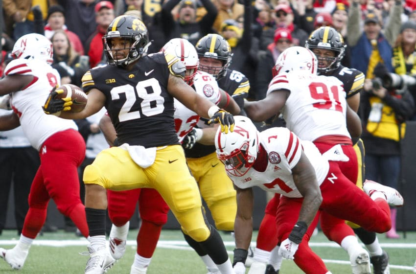 IOWA CITY, IOWA - NOVEMBER 23: Running back Toren Young #28 of the Iowa Hawkeyes runs in for a touchdown during the first half in front of linebacker Mohamed Barry #7 of the Nebraska Cornhuskers on November 23, 2018 at Kinnick Stadium, in Iowa City, Iowa. (Photo by Matthew Holst/Getty Images)