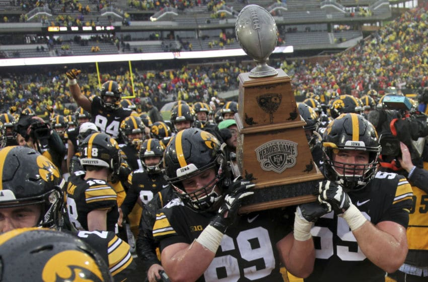 IOWA CITY, IOWA- NOVEMBER 23: Offensive linemen Keegan Render #69 and Ross Reynolds #59 of the Iowa Hawkeyes carry the Heroes Trophy off the field after their match-up against the Nebraska Cornhuskers on November 23, 2018 at Kinnick Stadium, in Iowa City, Iowa. (Photo by Matthew Holst/Getty Images)