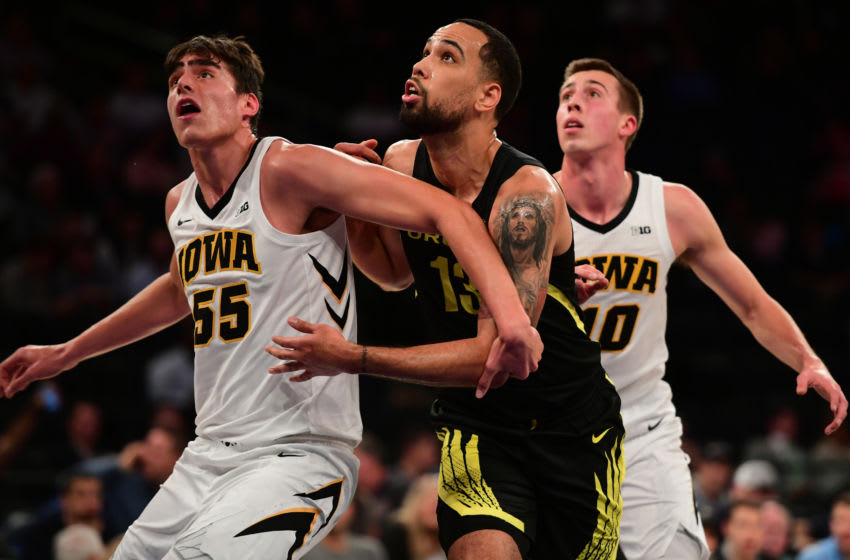 NEW YORK, NEW YORK - NOVEMBER 15: Luka Garza #55 of the Iowa Hawkeyes and teammate Joe Wieskamp attempt to block Paul White #13 of the Oregon Ducks during the first half of the game against Iowa Hawkeyes during the 2k Empire Classic at Madison Square Garden on November 15, 2018 in New York City. (Photo by Sarah Stier/Getty Images)