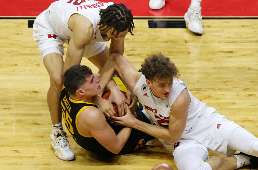 PISCATAWAY, NJ - JANUARY 02: Caleb McConnell #22 and Dean Reiber #21 of the Rutgers Scarlet Knights fights Luka Garza #55 of the Iowa Hawkeyes for a loose ball during the first half of a college basketball game at Rutgers Athletic Center on January 2, 2021 in Piscataway, New Jersey. Iowa defeated Rutgers 77-75. (Photo by Rich Schultz/Getty Images)