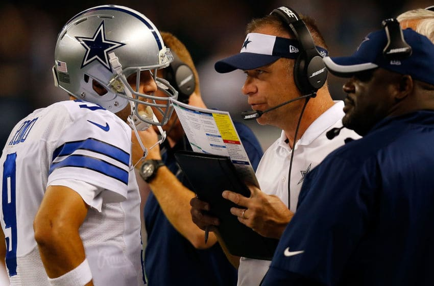 ARLINGTON, TX - OCTOBER 27: Tony Romo #9 of the Dallas Cowboys talks with assistant coach Scott Linehan during the second half against the Washington Redskins at AT&T Stadium on October 27, 2014 in Arlington, Texas. (Photo by Tom Pennington/Getty Images)
