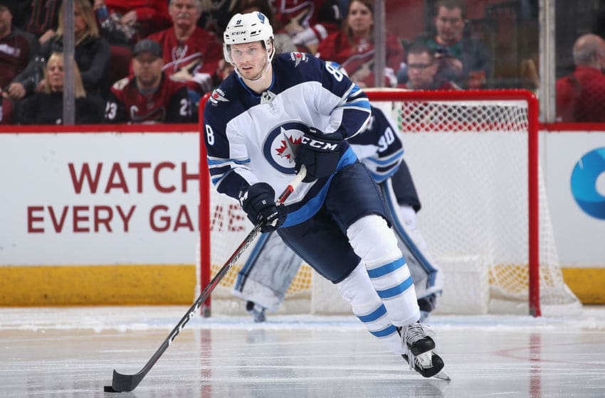 GLENDALE, ARIZONA - FEBRUARY 24: Jacob Trouba #8 of the Winnipeg Jets skates with the puck during the NHL game against the Arizona Coyotes at Gila River Arena on February 24, 2019 in Glendale, Arizona. The Coyotes defeated the Jets 4-1. (Photo by Christian Petersen/Getty Images)