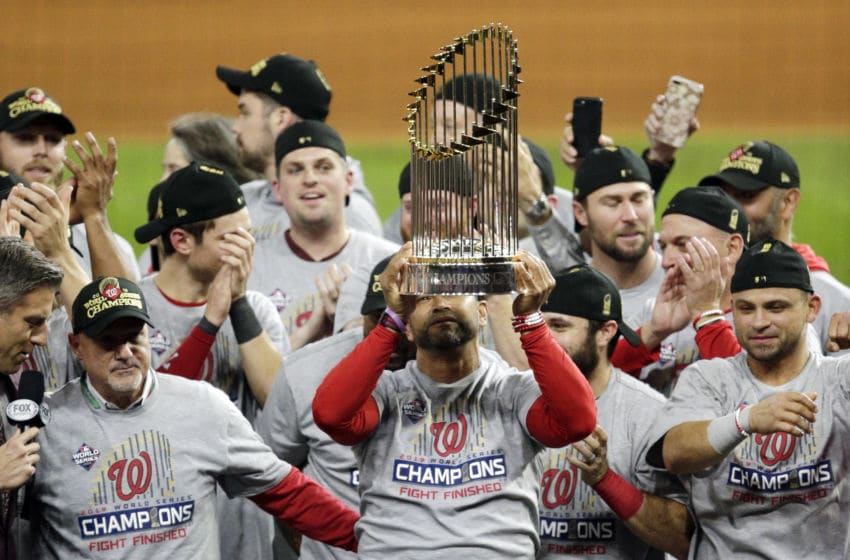 HOUSTON, TEXAS - OCTOBER 30: Manager Dave Martinez #4 of the Washington Nationals hoists the Commissioners Trophy after defeating the Houston Astros 6-2 in Game Seven to win the 2019 World Series in Game Seven of the 2019 World Series at Minute Maid Park on October 30, 2019 in Houston, Texas. (Photo by Bob Levey/Getty Images)
