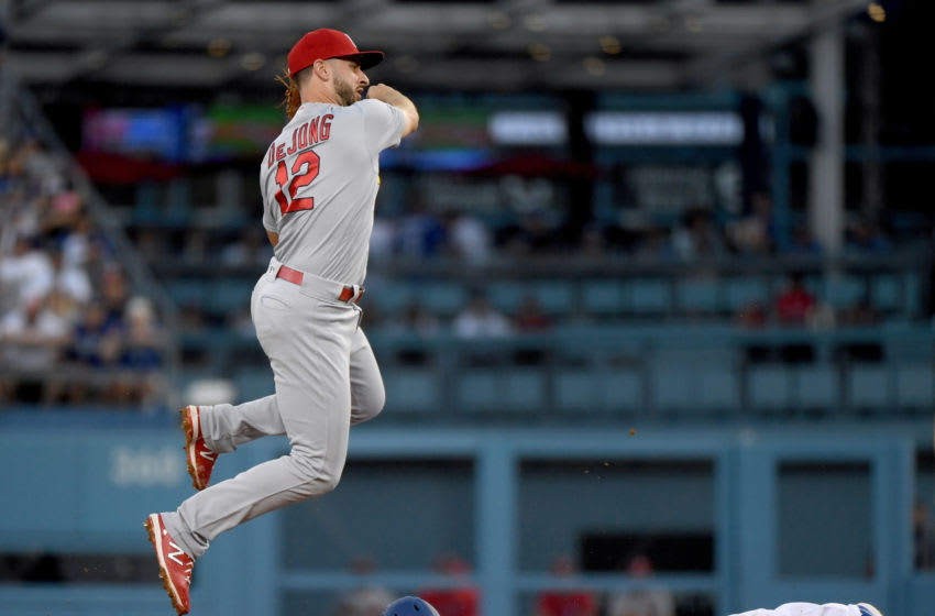 LOS ANGELES, CALIFORNIA - AUGUST 05: Paul DeJong #12 of the St. Louis Cardinals makes a throw over the slide of Kristopher Negron #9 of the Los Angeles Dodgers during the third inning at Dodger Stadium on August 05, 2019 in Los Angeles, California. (Photo by Harry How/Getty Images)