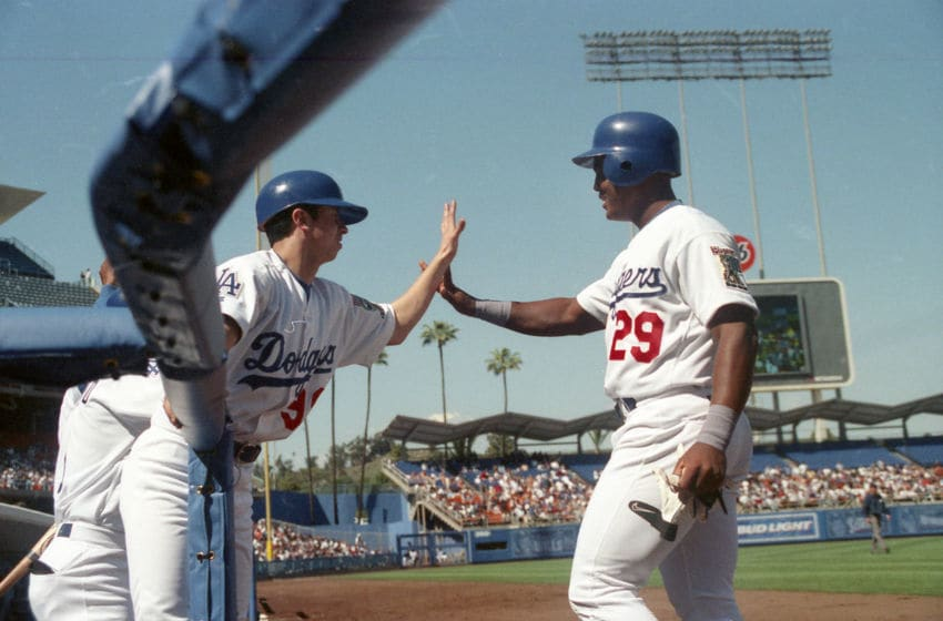 LOS ANGELES, CA - CIRCA 1999: Raul Mondesi of the Los Angeles Dodgers id congratulated by the bat boy after hitting a home run at Dodger Stadium circa 1999 in Los Angeles, California. (Photo by Owen C. Shaw/Getty Images)
