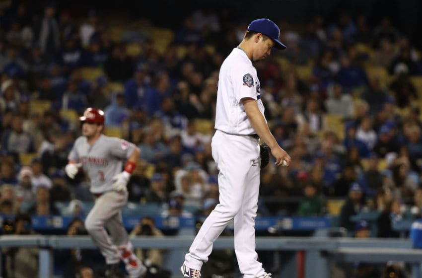 LOS ANGELES, CA - MAY 11: Pitcher Kenta Maeda #18 of the Los Angeles Dodgers reacts after giving up a two-run homerun to Scooter Gennett #3 of the Cincinnati Reds, in the background rounding third base, in the fifth inning during the MLB game at Dodger Stadium on May 11, 2018 in Los Angeles, California. (Photo by Victor Decolongon/Getty Images)