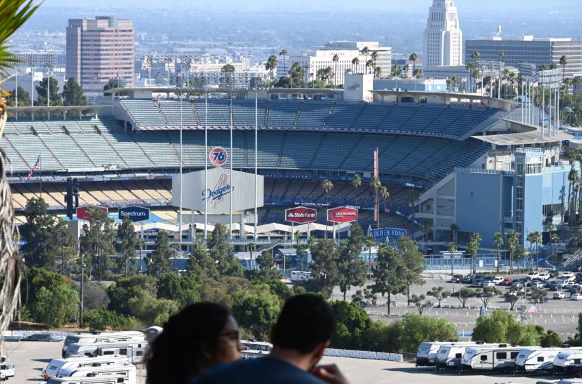 A couple looks out over the Los Angeles city skyline and Dodgers Stadium ahead of the opening day game between the Los Angeles Dodgers and the San Francisco Giants, July 23, 2020 in Los Angeles, California. - The game will be played without fans in the stadium due to the COVID-19 pandemic. (Photo by Robyn Beck / AFP) (Photo by ROBYN BECK/AFP via Getty Images)