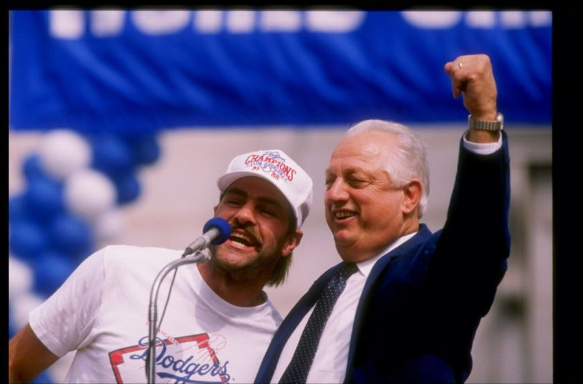 LOS ANGELES, CA - OCTOBER 25: Outfielder Kirk Gibson #23 and manager Tommy Lasorda #2 of the Los Angeles Dodgers speak to the croad at the Victory Parade for the Los Angeles Dodgers on October 25, 1988 in Los Angeles, California. (Photo by Mike Powell/Getty Images)