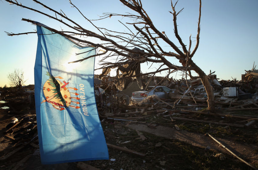 MOORE, OK - MAY 22: An Oklahoma state flag hangs in a tree next to a destroyed home across the street from the Plaza Towers Elementary School where several children died during a tornado that ripped through the area on May 22, 2013 in Moore, Oklahoma. The tornado of at least EF4 strength and two miles wide touched down May 20 killing at least 24 people and leaving behind extensive damage to homes and businesses. U.S. President Barack Obama promised federal aid to supplement state and local recovery efforts. (Photo by Scott Olson/Getty Images)