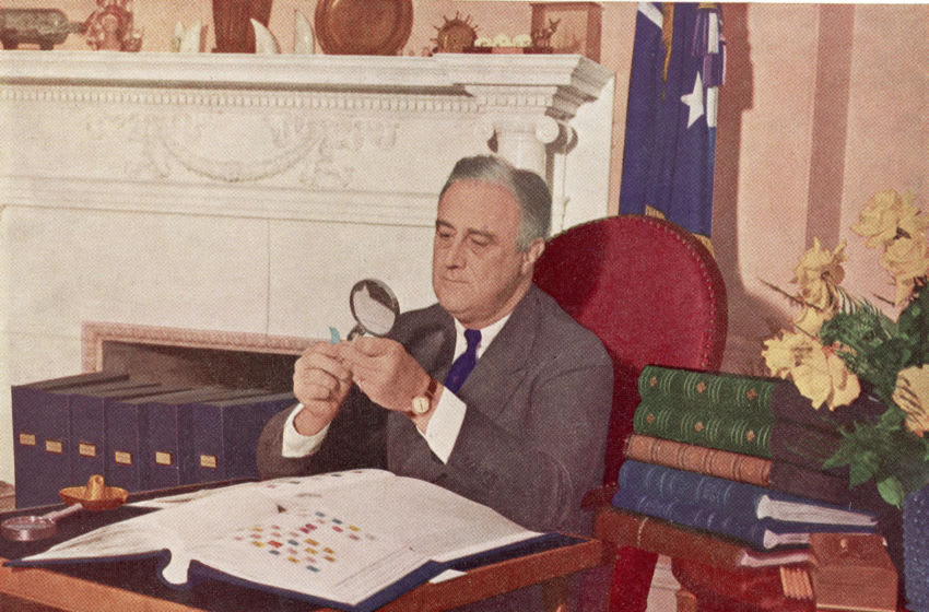 US President Franklin Delano Roosevelt (1882 - 1945) holds a stamp under a magnifying glass while seated at his desk with his stamp collection, Washington, DC, circa 1944. (Photo by Hulton Archive/Getty Images)