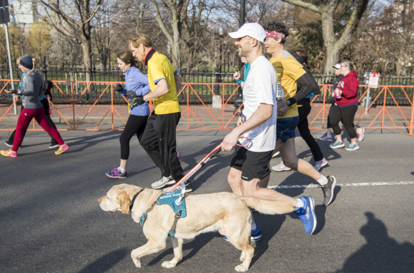 BOSTON, MA - APRIL 14: Guiding Eyes for the Blind President & CEO Thomas Panek participates in the BAA 5K guided by his guide dog Gus, accompanied by ultra-runner Scott Jurek, kicking off the Guiding Eyes Wag-a-thon on April 14, 2018 in Boston, Massachusetts. (Photo by Scott Eisen/Getty Images for Guiding Eyes for the Blind)