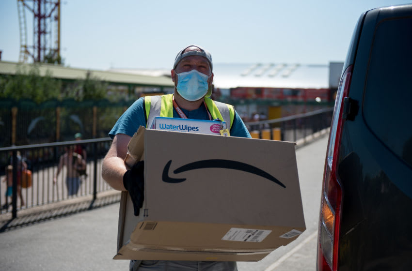 An Amazon delivery person wearing a face mask delivers a parcel along the promenade on June 25, 2020 in Southend-on-Sea, England. (Photo by John Keeble/Getty Images)