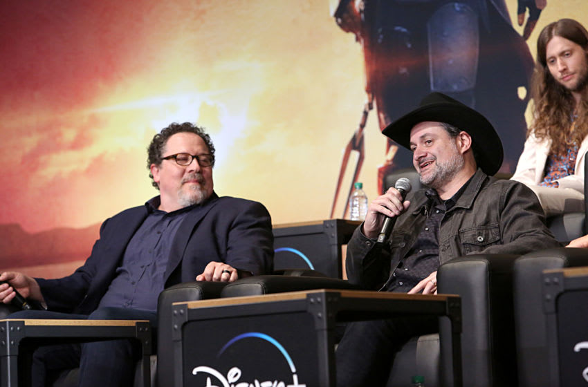 HOLLYWOOD, CALIFORNIA - NOVEMBER 13: (L-R) Executive Producer Jon Favreau and Executive Producer/Director Dave Filoni speak onstage at the premiere of Lucasfilm's first-ever, live-action series,