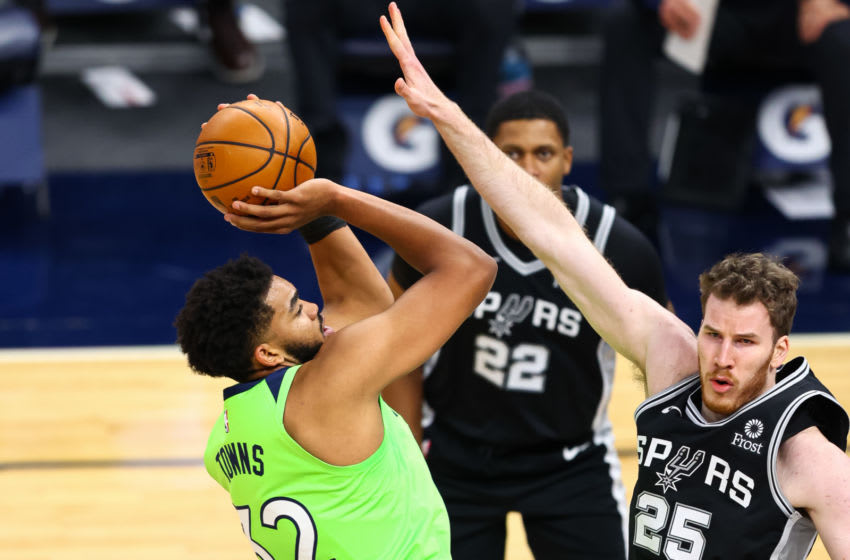 Jakob Poeltl of the San Antonio Spurs fouls Karl-Anthony Towns of the Minnesota Timberwolves. (Photo by Harrison Barden/Getty Images)